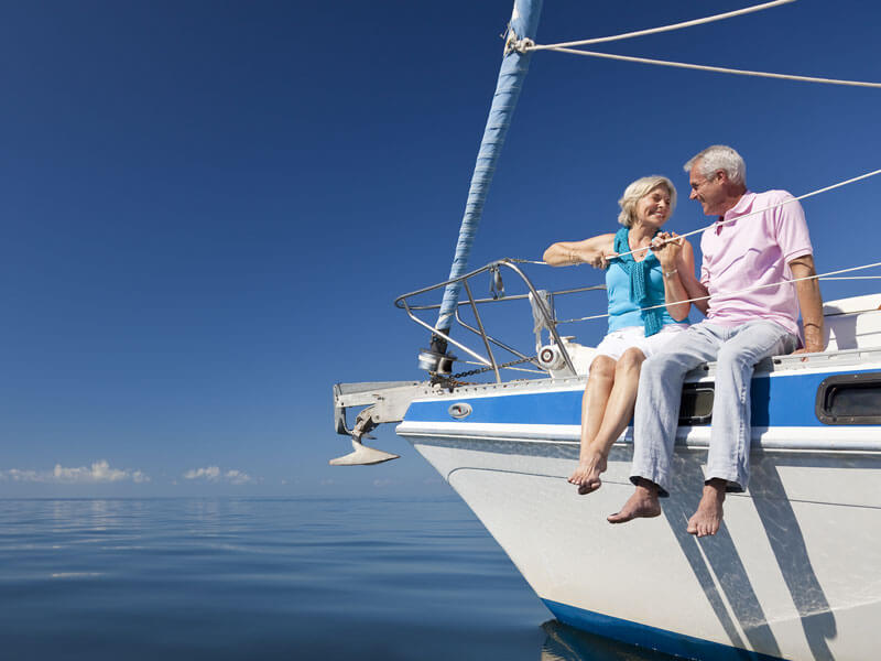 Retired couple sitting on a yacht enjoying the blue skies of financial freedom.