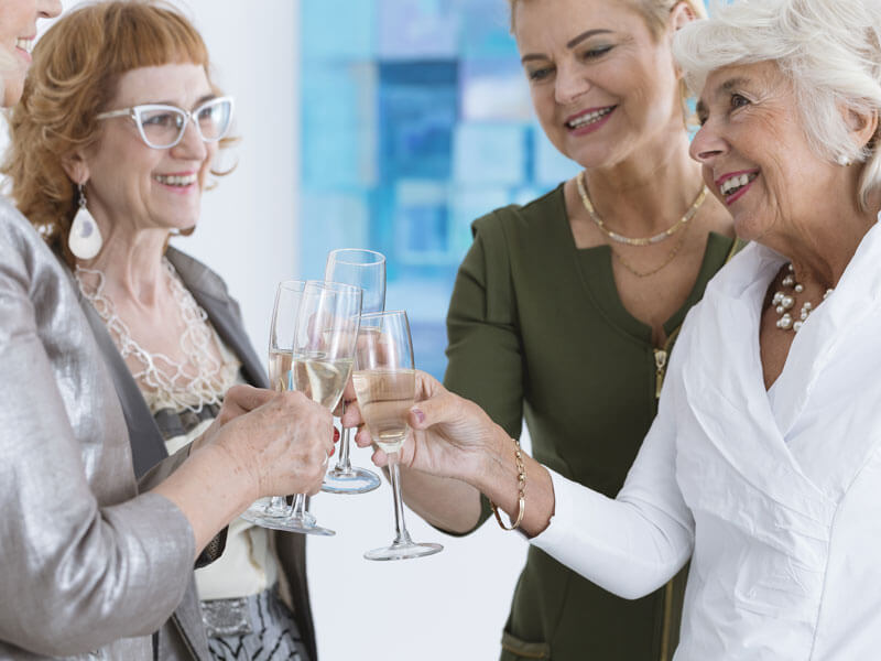 Financially successful retirees toast with champagne to celebrate working with fiduciary wealth advisors in Sarasota.